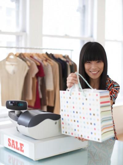 Sales Clerk Giving Shopping Bag