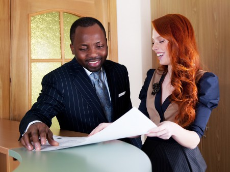 Two business people laughing in office space with papers