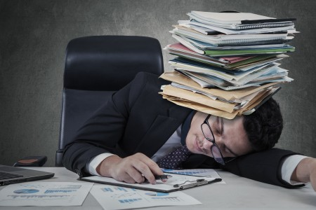 Exhausted man sleeping with paperwork